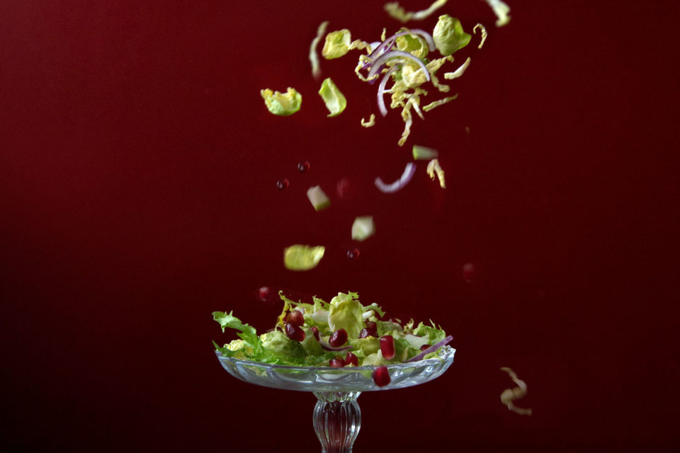 Salad leaves being dropped onto a dish